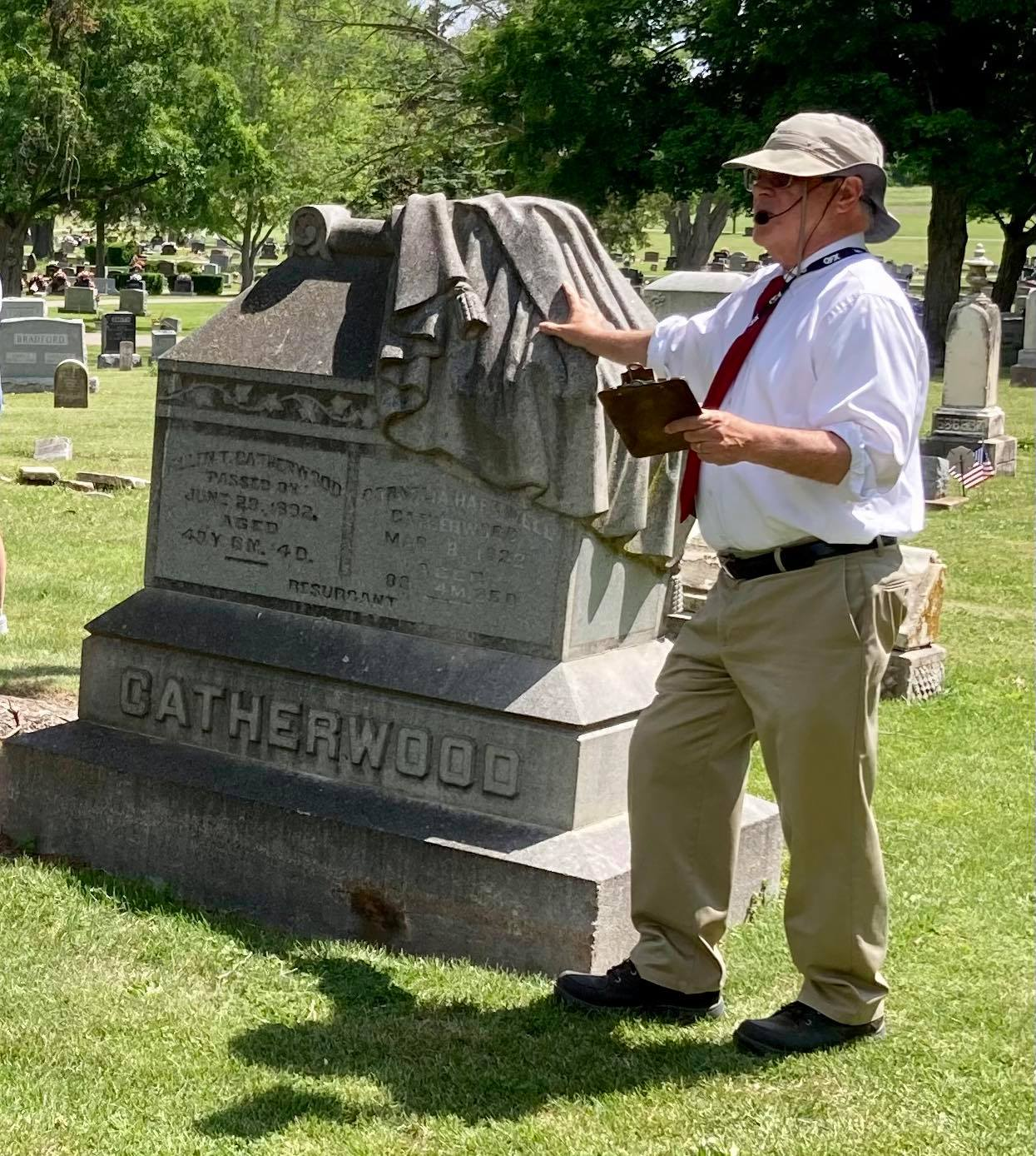 Tom Sweeney, co-host of the Floral Hill Cemetery Walk on June 5th. Tom is explaining the meaning of the cloak partial draped over a headstone.